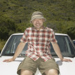 Stock Photo: Man resting on hood of his car