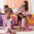 Four girls sitting in bedroom with computer, journal, cell phone and fingernail polish — Stock Photo