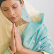 Indian woman in traditional clothing praying - Stock Photo