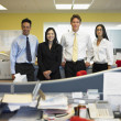 Businessmen and women standing in office — Stock Photo