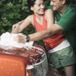 Hispanic couple washing car in driveway — Stock Photo