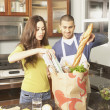 Young Hispanic couple unpacking grocery bag - Stockfoto