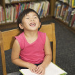 Laughing little girl reading a library book — Stock Photo #13237069