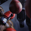 Male boxer using a punching bag — Stock Photo