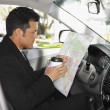 Stock Photo: Hispanic man reading map in car