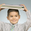 Boy balancing notebooks on his head - Stock Photo