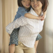 Asian mother giving young daughter piggyback ride indoors - Stockfoto