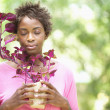 Stock Photo: Woman holding plant with eyes closed