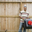 African man wearing party hat and barbequing - Stock Photo