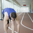 Man tying shoe on indoor track — Stock Photo