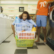 Royalty-Free Stock Photo: Young woman trying to lift three laundry baskets