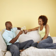 Couple on couch toasting with white wine — ストック写真