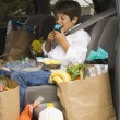 Boy sitting in backseat of car eating with groceries - Stock Photo