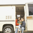 Family sitting in doorway to recreational vehicle — Foto de Stock