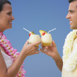 Couple toasting each other with tropical drinks — Stock Photo