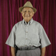 Elderly man standing and smiling — Stock Photo
