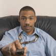 Close up of businessman holding remote — Stockfoto