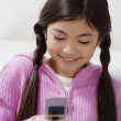 Young Hispanic girl dialing cell phone - Stock Photo