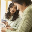 Asian mother and adult daughter playing cards - Stock Photo