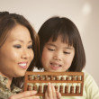 Mother and daughter using an abacus together — Stock Photo