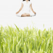 Young meditating woman levitating above tall grass — Stock Photo