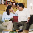 Hispanic couple talking on sofa — Stok fotoğraf