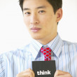 "Stock Photo: Portrait of businessmholding ""think"" sign"