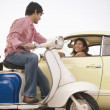 Man on scooter talking to woman in car - Foto Stock
