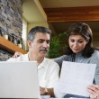 Middle-aged couple looking at paperwork and laptop — Stock Photo