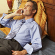 Businessman talking on cell phone in bed — Stok fotoğraf