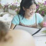 Asian woman with menu at restaurant — Stock Photo