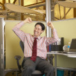 Businessman celebrating at desk — Stockfoto