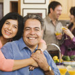 Middle-aged Hispanic couple hugging at party - Stock Photo