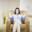 Pacific Islander woman smiling in armchair — Stock Photo