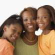 Mother and daughters smiling for the camera — Stock Photo #13237493