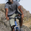 Male cyclist in rugged terrain — Stock Photo #13237495
