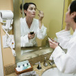 Woman in bathrobe applying makeup — Stockfoto