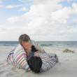 Couple wrapped in a blanket on the beach — Stock Photo #13237520