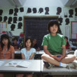 Boy sitting on desk in classroom — Foto de Stock