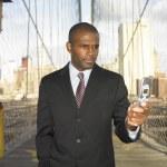 Businessman on bridge dialing cell phone — Stock Photo