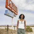 Hispanic woman next to motel sign on beach - 图库照片