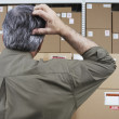 Businessman in warehouse scratching his head — Stockfoto