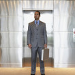 Young businessman standing outside of elevator — Stock Photo