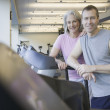 Couple standing on treadmill at gym — Stock Photo