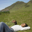 African couple laying in sunlit grass with eyes closed in rural area — Stock Photo