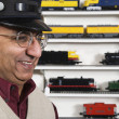 Man with conductors hat in hobby shop - Stock Photo