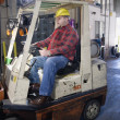 Man driving forklift in warehouse — Stock Photo
