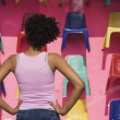 Royalty-Free Stock Photo: African woman looking at plastic chairs in store window
