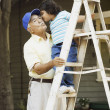 Little girl giving grandpa a kiss while standing on a ladder - Stock Photo