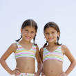 Stock Photo: Hispanic sisters wearing matching bathing suits